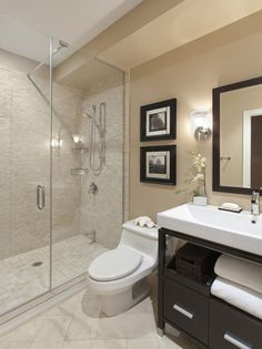 glass shower stalls and white latrine connected by double black wooden picture frames on beige wall