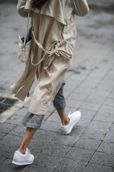 Pair a nude trenchcoat with grey culottes for both chic and easy-to-wear look. Mix things up by wearing white athletic shoes.   Shop this look on Lookastic: https://lookastic.com/women/looks/beige-trenchcoat-grey-culottes-white-athletic-shoes/17446   — Beige Trenchcoat  — Beige Canvas Crossbody Bag  — Grey Culottes  — White Athletic Shoes