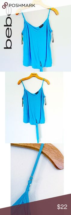 Bebe Side Knot Tank Bebe Tank Top Camisole with a stylish side knot on front lower left side that gives you the option to where as a regular fit or raise enough to show some skin.  Adjustable straps and V neckline  Size: Will fit between Petite Medium-Medium Color: Turquoise Blue Inside care instruction tags removed for comfort. Worn once and hand washed. Perfect Condition. bebe Tops