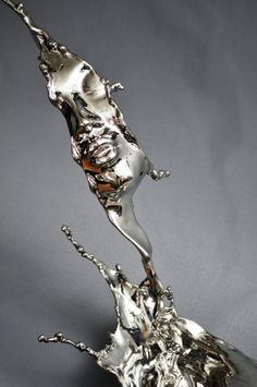 Human faces emerge from the splashes of stainless steel