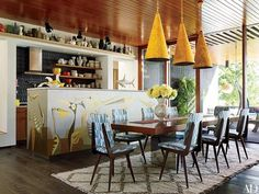 A trio of kicky yellow pendant lamps accent a John-Paul Philippé mural in the kitchen of Jonathan Adler and Simon Doonan's beachfront retreat | archdigest.com