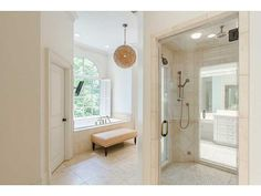A spacious bathroom with a glass and neutral tile shower. Interesting chandelier, don't you think? Source: http://www.zillow.com/digs/Home-Stratosphere-boards/Luxury-Bathrooms/