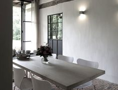 Cooreman mixes ancient elements (the original brick floor) with new pieces (the white molded plywood dining chairs), plus newer pieces that look old (like the glazed, wrought-iron windows and doors on the ground level).