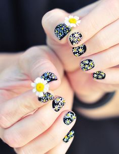 DIY Daisy Nail Art on black manicure. I'm not really in to nail art but this is fab!