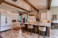 Rustic open concept kitchen with wood front refrigerator, white cabinets and granite counter tops