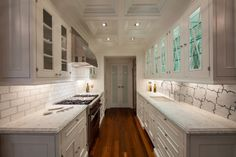 The lighting in this kitchen helps it feel really open and airy. --gally kitchen layout with white marble via DecorPad