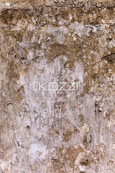 peeled papers on messy wall. - Close-up shot of scratched advertisement paper on dirty stained concrete wall.