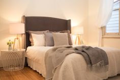 Large master bedroom, grey velvet bed head, headboard, white round metal side table, large table lamp, cream linen