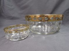 """Vintage Arcoroc France Master Fruit Bowl and Matching Berry Bowl.  Here are 2 bowls in the Cris D'Arques/Durand Arcoroc Petale Design.  They are clear bowls with a band of gold keys and green diamonds decor.  The master bowl is approx. 8 3/4"""" across x 3 3/4"""" tall.  The small berry bowl is approx. 4 1/4"""" across x 2"""".  There is wear to the design along with some scratching.  There is also some spots on the outside bottom of the bowl which look like tiny little rough spots, stiples, bumps.  ..."""