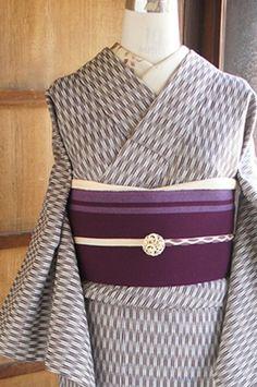 ブラウンと生成り色の矢羽根模様が織り出されたナチュラルモダンなウールの単着物です。