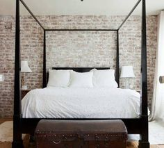 master bedroom with a dark wood canopy bed with a trunk at its foot with a brick wall providing the backdrop