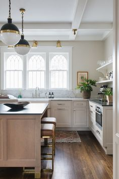 arched windows over the taupe cabinets with brass fixtures