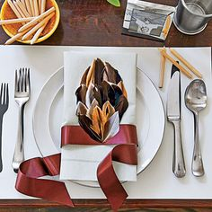 The Kids' Table | Fresh & Modern Thanksgiving Mimic the adult table but with more kid-friendly picks: pewter julep cups, everyday white plates, and paper napkins and place mats. Wrap napkins with ribbons, and attach feather plumes for a festive headdress.