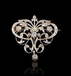 Broche de corsage en or jaune et or blanc 18K (750 millièmes) à motifs d'entrelacs feuillagés et ajourés sertis de diamants taille rose, retenant un pendant mobile.  Années 20. Art Nouveau or Art Nouveau Style.