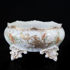 """Lot #22: Limoges Porcelain Center Bowl DESCRIPTION: Limoges porcelain center bowl decorated along the body with handpainted floral designs accented with gilt foliate. The bowl sits on four feet designed with ornate grapes. Marked on the bottom """"Limoges France""""  CIRCA: Early to mid 20th Ct. ORIGIN: France DIMENSIONS: L: 7″ H: 4.5″"""