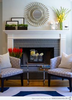 The modern fireplace is flanked by accent chairs and features a sunburst mirror above.