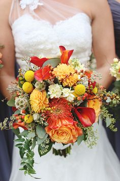 Overflowing with calla lilies, dahlias, roses, pincushion protea, craspedia, scabiosa pods, hypericum berries and seeded eucalyptus, this festive wedding bouquet screams fall. Beautiful! {Diana M. Lott Photography}