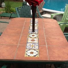 Used leftover terra cotta floor tile and accented with talavera tiles to fix patio table after a storm blew it over and shattered the glass top. Turned out real pretty!