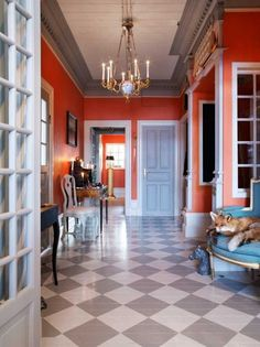 White door frames and that grey-ish blue door. Gold chandelier, and that turquoise upholstered, gold bergere chair offseting the coral.