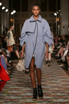 A model walks the runway at Dior's cruise 2017 show wearing a blue cotton tweed coat