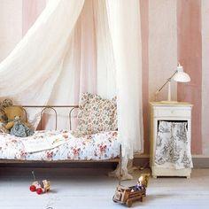 Chambre rose pour petite fille, avec un ciel de lit, du linge de lit fleuri et un parquet peint en blanc