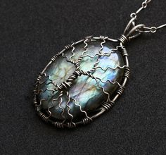 This striking pendant necklace is handcrafted by wrapping sterling silver wire into a spreading tree of life design over a gorgeous labradorite cabochon. This labradorite piece has flashes of green, teal, and gold. You will be enchanted by the seemingly magical variations and flashes of color!  Exact pendant measurements are shown in second to last photo. The silver has been oxidized and polished for stunning contrast and an antique-look.  Comes with an Italian-made, 18 inch sterling silver…