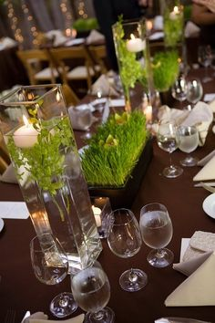green centerpieces.  i like the tall candles, but the short black grassy things are pretty too.