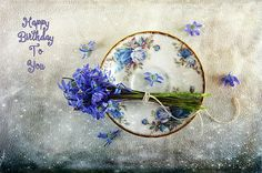 Lovely blue spring flowers on a vintage saucer adds to the anticipation of a happy birthday celebration. Greeting card for those who love blue.