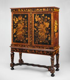 Cabinet on stand  Dutch early 1700s Box-like cabinets on open stands became fashionable towards the end of the seventeenth century. Rather than on the overall shape, the attention of the cabinetmaker was lavished on exquisite marquetry decoration, especially blomwerk (floral work). The most striking floral marquetry has been attributed to Jan van Meekeren. More than two hundred flowers embellish this cabinet, several of which occur more than once, sometimes in reverse