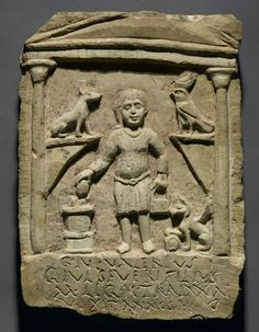 Funerary Stela of C. Julius Valerius. The child's costume and pose are Roman, but his long sidelock of hair is traditionally Egyptian, as are the jackal god Anubis and the falcon god Horus above his head. The griffin in the lower right corner represents the classical goddess Nemesis, who controlled life and death.  ◦Medium: Limestone, traces of paint  ◦Place Made: Egypt, Provenance unknown  ◦Dates: 3rd century C.E.  ◦Period: Roman Period