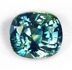 """A very compelling, unheated, """"fancy"""" sapphire hailing from Montana, weighting 1.58 cts., medium, vivid, bi-color, yellow & green, blending however, very well in an intense """"teal"""", greenish-blue color, masterly executed, """"antique"""" cushion, mixed cut, and measuring 6.38x5.64x4.63mm, eye flawless, VVS1 from the Rock Creek deposit, Philipsburg, Montana."""