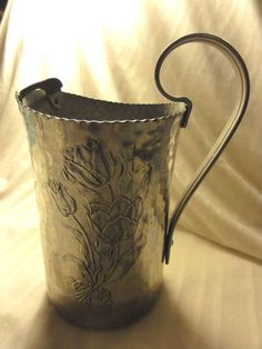 "SOLD 16.16 Vintage Ornate Hammered Aluminum Water Pitcher / Vase With Flowers       Measures: 5"" Diameter, 7"" tall        Condition: Very Good. It has no markings, some light discoloration at bottom, no dents, and no holes."
