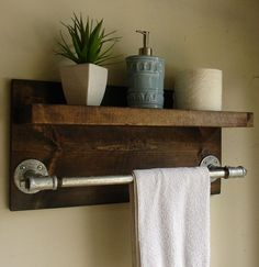 Industrial rustic bathroom shelf outfitted with a pipe towel rack.