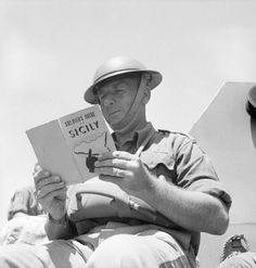 A British soldier reads up on Sicily, the target for the next Allied invasion, July 1943.