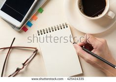 Young man right hand writing on blank notebook on wood table with coffee cup, smartphone, and glasses beside in morning time