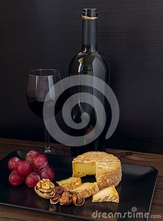 Soft washed-rind cheese, hazelnuts, walnut, red grape and wine in the glass and bottle