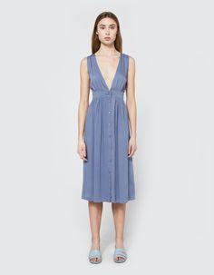 Dress from Farrow in Blue. Thick tank straps. Deep V-neckline. Front button closure. Gathered detailing at waist. Full skirt. On-seam side pockets. Unlined.    • Fine line twill  • 100% rayon  • Hand wash cold, line dry