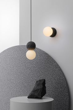 David Pompa's Origo light contrasts rough volcanic rock and glass bulbs
