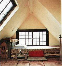 bed in a nook with slanted ceiling and window/skylight
