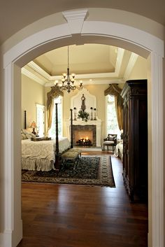 Tray ceiling with recessed lights; gorgeous fireplace surround; wood floor; beautiful silk panel draperies with swags... what a bedroom!