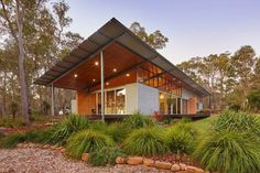 A light-filled home clad in corrugated steel in the Australian bushland