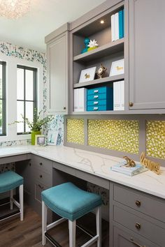 Gray, blue, and green home office space features an L shaped gray desk with brass knobs topped with a white marble countertop seats blue sawhorse desk stools, one under a gray window framed by white molding lined with blue and white floral wallpaper and the other on an adjacent wall beneath gray cabinets flanking open shelves filled with blue, white, and green organizational decor.