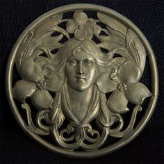 Art Nouveau Face An Art Nouveau die sample of a woman's head amid flowers, perhaps representing Summer.