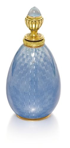 A gold-mounted enamel scent bottle, V. Soloviev, St Petersburg, 1908-1917 the surface of translucent steel blue enamel over banded wavy engine-turning, two-colour gold chased leaf rim, the gadrooned stopper set with a blue chalcedony cabochon, the base inset with a gold coin of Nicholas II, 56 standard.