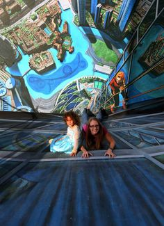 A woman and her daughter pose on a chalk 3-D artwork on March 4, 2015, near the Jumeirah Beach Residence (JBR) in Dubai during the Canvas Festival, a three-dimensional pavement art event. - tribunemedia.com
