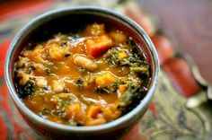 A hearty winter soup recipe with kale, white beans, and roasted carrots, butternut squash, tomatoes, onions, and garlic.