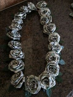 Dollar money origami graduation lei.  This is $100 in ones.  Each rose is 5 ones dollar bills.  The roses are made like the twisted crepe paper roses.