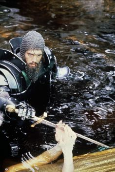 """""""Excalibur"""" directed by John Boorman, 1981. Arthur receives a replacement sword from The Lady In The Lake. Or the Lady takes back the Sword as he lies dying: I'm not sure which...."""