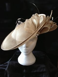 Hadleigh Hats- A really striking saucer shape that has a domed crown giving the appearance of a hat but held in place by a metal hairband. The thin loops have pearls and diamonte scattered on them to match the pearl and diamonte clasp.