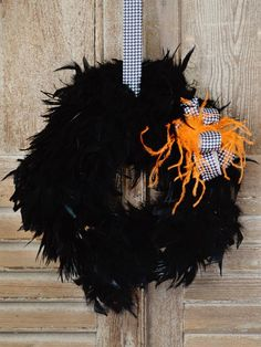 """Materials Needed: 18"""" straw wreath form two 10-yard packages of black feather trim one black feather boa scissors high-temperature hot glue gun and glue sticks  ribbon and additional feathers for embellishment"""
